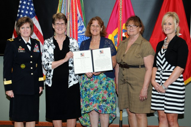 Brig. Gen. Kristin K. French, JMC commanding general, presents Albert Ehringer's family his certificate that recognizes him as a member of the Ammunition Hall of Fame during a ceremony held July 9, at the Rock Island Arsenal. Pictured left to right: daughters Patricia McKenna, Carolyn Kazako, Cindi Bertuli, and granddaughter Christie Rice.
