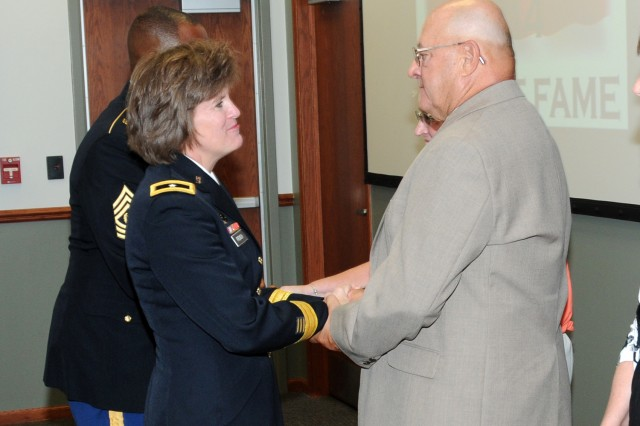 Brig. Gen. Kristin K. French, JMC commanding general, congratulates Richard Janik for his induction into the Ammunition Hall of Fame following the ceremony held at the Rock Island Arsenal, 9 July.