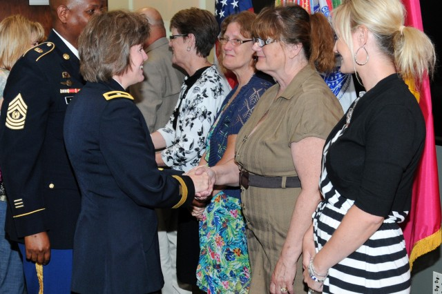 Brig. Gen. Kristin K. French, JMC commanding general, congratulates the family of Albert Ehringer for his induction into the Ammunition Hall of Fame following the ceremony held at the Rock Island Arsenal, 9 July. Pictured left to right: daughters Patricia McKenna, Carolyn Kazako, Cindi Bertuli, and granddaughter Christie Rice.