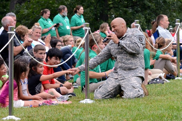 "A Soldier from the U.S. Army Band ""Pershing's Own,"" engages audience members during the U.S. Army Military District of Washington Twilight Tattoo held on Whipple Field at Joint Base Myer-Henderson Hall, Va., July 9, 2014."