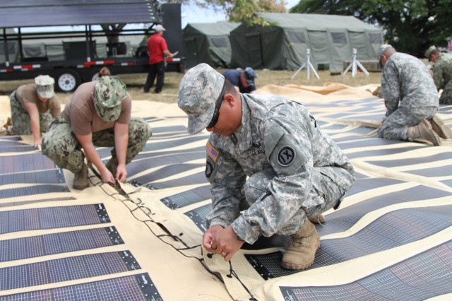 Sgt. Roy Gano, a Kapolei, Hawaii, native and carpenter/masonry technician with the 871st Engineer Company, 9th Mission Support Command, along with other Soldiers and other support elements, becket lace the solar shade canopy together during the setup of a humanitarian aid and disaster relief event for Rim of the Pacific training exercise at Ford Island, Hawaii, July 7, 2014. The solar shade has the potential to provide enough energy for several days of continuous 24-hour use. Twenty-two nations, more than 40 ships and submarines, about 200 aircraft and 25,000 personnel are participating in Exercise RIMPAC, from June 26 to Aug. 1, 2014, in and around the Hawaiian Islands and Southern California. The world's largest international maritime exercise, RIMPAC provides a unique training opportunity that helps participants foster and sustain the cooperative relationships that are critical to ensuring the safety of sea lanes and security on the world's oceans. RIMPAC 2014 is the 24th exercise in the series that began in 1971.