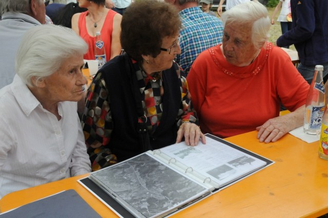 Three of the oldest surviving original residents of Schmidheim peruse a book of old photos during the annual Schmidheimer reunion in the Hohenfels Training Area, Germany, July 5, 2014. From left to right are: Frieda Ohneis, Regina Roedl, Franziska Kremser.