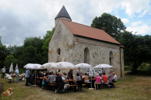 The former residents of Schmidheim and their relatives gather at the reconstructed village church during the annual Schmidheimer reunion in the Hohenfels Training Area, Germany, July 5, 2014.