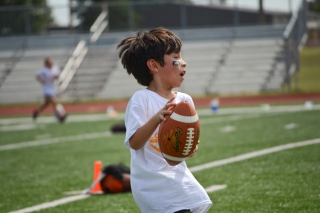 Six-year-old Cristian Rojas catches a football during an offensive drill at the Cortez Allen Football ProCamp at Fryar Staduim July 9. Fort Campbell was one of nine installations that won a free two-day camp after participating in a Proctor and Gamble sponsored contest held in DECA commissaries nationwide.