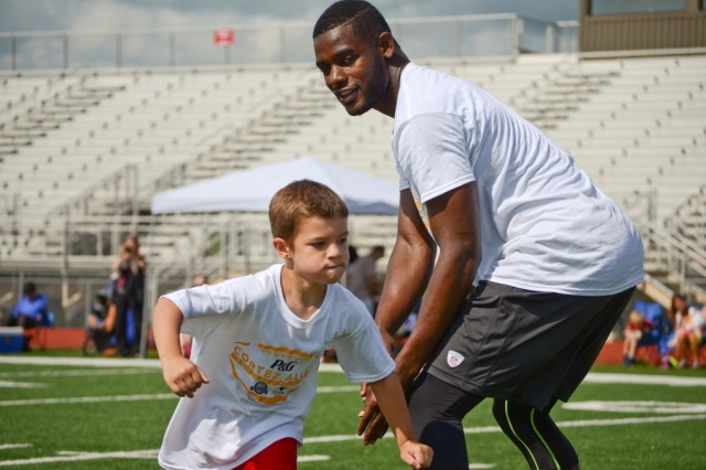 Jayden Gaylor, 6, maneuvers past Pittsburgh Steelers cornerback Cortez Allen during an offensive drill during the Cortez Allen Football ProCamp at Fort Campbell's Fryar Staduim, July 9. The two-day camp, which focused on football fundamentals, hosted 120 children ages kindergarten through 8th grade from Fort Campbell military families.