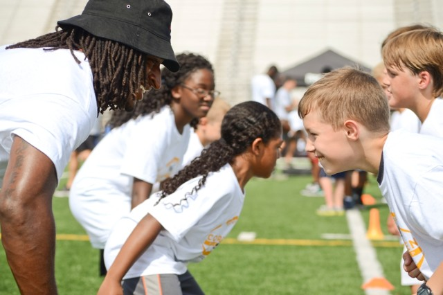 Washington Redskins' wide receiver Andre Roberts and 10-year-old Austin Jones prepare to go head-to-head during a tackling drill during the Cortez Allen Football ProCamp at Fort Campbell's Fryar Staduim, July 9. Roberts, whose parents both retired from the U.S. Army after serving more than 20 years each, was drafted by the Arizona Cardinals in the third round of the 2010 NFL Draft and now plays for the Redskins.