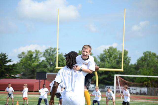 """Austin Jones, 10, is carried off by Washington Redskins' wide receiver Andre Roberts during a football drill at the Cortez Allen Football ProCamp at Fryar Staduim July 9. """"First I got to tackle him and then he just carried me off -- and he lost his hat! I will remember that forever."""""""