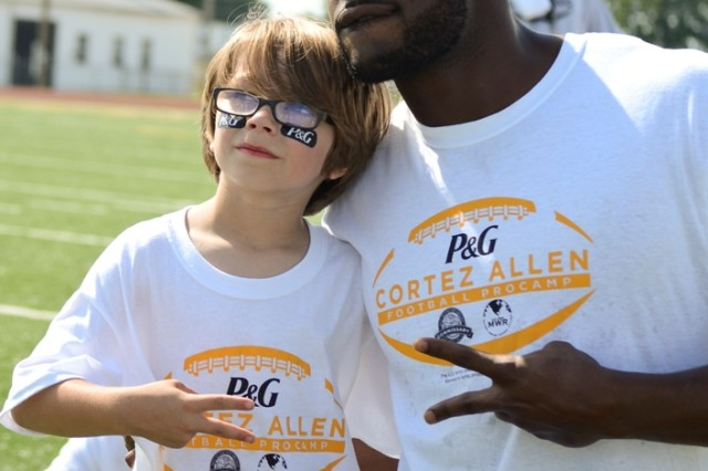 """Six-year-old Gage Fuentez poses for a picture with Cortez Allen, cornerback for the Pittsburg Steelers, after being """"drafted"""" as the number one first round draft pick during the Cortez Allen Football ProCamp at Fort Campbell's Fryar Staduim, July 9. Allen, who graduated from The Citadel, The Military College of South Carolina, before being drafted into the NFL by the Steelers in 2011, learned firsthand about military life, training and discipline during his time at the institution."""