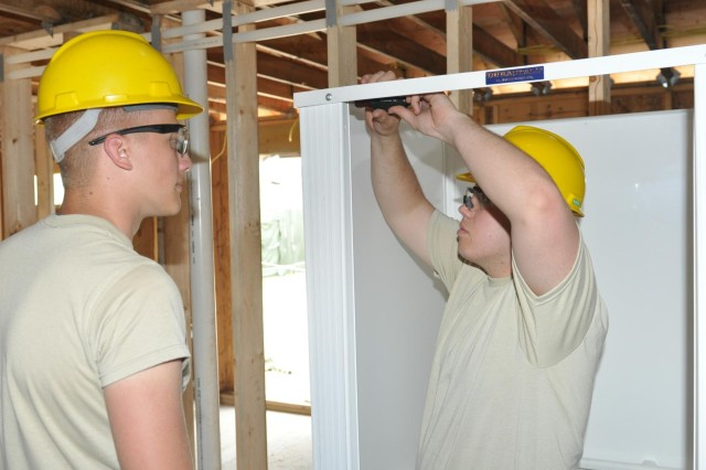 Army engineers Spc. Daniel Sgaard and Pfc. Kody Willis, from the 327th Engineer Company, install showers in a shower facility to be used by service members training at Forward Operating Base Liberty at Fort McCoy, Wis.