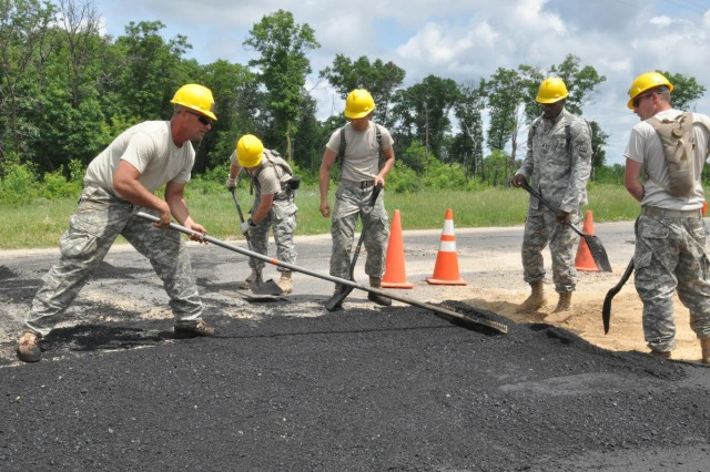 Army engineers Sgt. Zachary Wheeler, Spc. Adam Duell, Spc. Steven Drury, Spc. Johnathan Gause and Spc. Troy Rasmussen, of the 727th Engineer Detachment, grade and pave 6,825 feet, or about one and a quarter mile, of road at simulated village located in the South Post area of Fort McCoy, Wis., as part of their annual training that will be used in the training of Soldiers, Sailors, Marines and Airmen during this year's training cycle. (Photo by Sgt. 1st Class Darrin McDufford, 416th Theater Engineer Command)