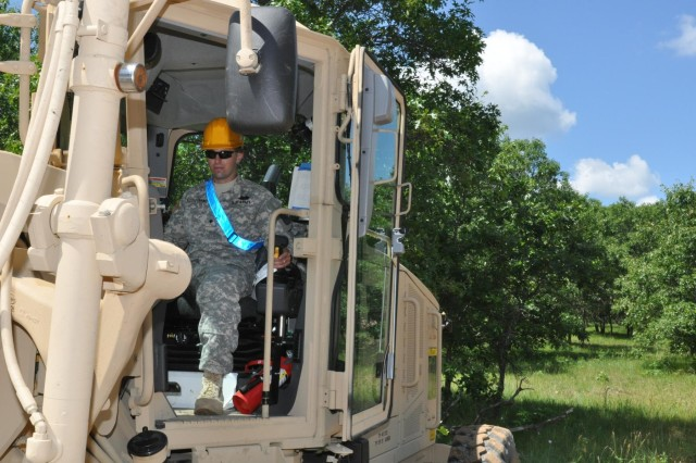 Spc. William Cockerham, and engineer with the 721st Engineer Company, grades a portion of a convoy route that required improvements for Soldiers who train in conducting convoy operations through the South Post area of Fort McCoy, Wis.