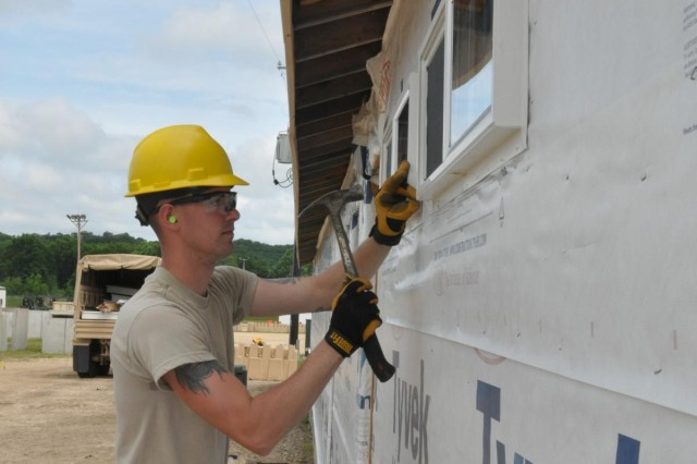 Spc. Forrest Lauff, an electrician and carpenter from the 327th Engineer Company, installs windows in in a shower facility to be used by service members training at Forward Operating Base Liberty at Fort McCoy, Wisconsin, as part of their annual training requirement allowing them to be technically proficient in their jobs that include electrictians,plumbers, wood workers and other specialties.