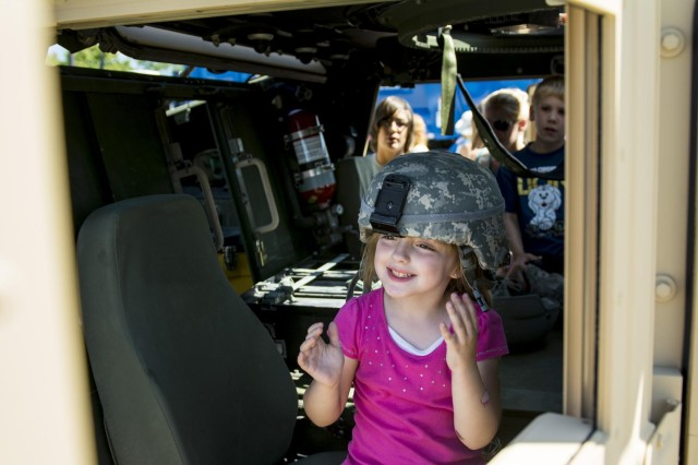 Madison, 5, of Darien, Illinois, tries on an Army combat helmet while playing in an Army Reserve Humvee belonging to the 416th Theater Engineer Command during the Touch a Truck community event hosted by the Village of Willowbrook, Parks and Recreation Department, July 11. An estimated 300 children visited and interacted with various trucks on display. (U.S. Army photo by Sgt. 1st Class Michel Sauret)
