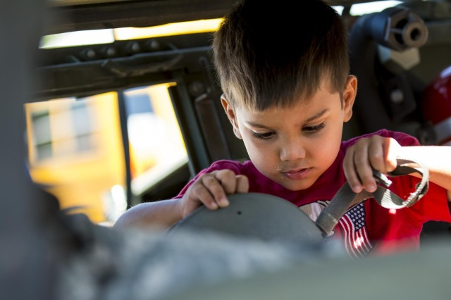 A boy tries on an Army combat helmet while playing in an Army Reserve Humvee belonging to the 416th Theater Engineer Command during the Touch a Truck community event hosted by the Village of Willowbrook, Parks and Recreation Department, July 11. An estimated 300 children visited and interacted with various trucks on display. (U.S. Army photo by Sgt. 1st Class Michel Sauret)