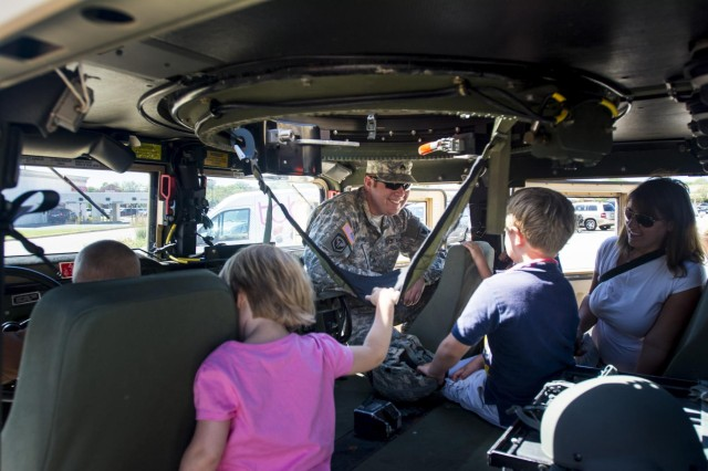 Sgt. Eric Urbanski, a Soldier with the 416th Theater Engineer Command, from Skokie, Ill., shows children the belt buckling system of an Army Reserve Humvee during the Touch a Truck community event hosted by the Village of Willowbrook, Parks and Recreation Department, July 11. An estimated 300 children visited and interacted with various trucks on display. (U.S. Army photo by Sgt. 1st Class Michel Sauret)