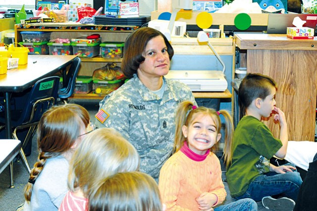 Headquarters Battalion Command Sgt. Maj. Carolyn Reynolds sits with Fort Belvoir Elementary School students after teaching them about fairness during a character lesson of the school's Character Counts program in 2013.