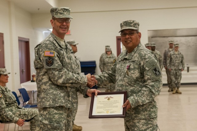 Maj. Gen. David Conboy, commanding general of the 416th Theater Engineer Command (TEC), presents a Meritorious Service Medal to Chief Warrant Officer 5 Juan Luna for his duties performed as the outgoing command chief for the 416th TEC during the change of responsibility ceremony held at the Parkhurst U.S. Army Reserve Center in Darien, June 8. (U.S. Army photo by Sgt. 1st Class Michel Sauret)