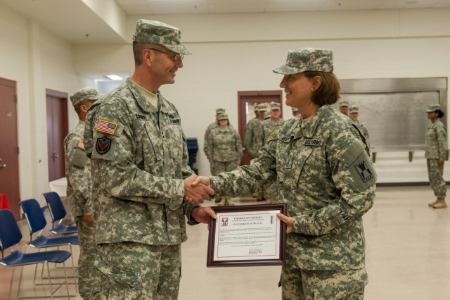 Maj. Gen. David Conboy, commanding general of the 416th Theater Engineer Command (TEC), presents a charge of orders to Chief Warrant Officer 5 Therese Beatty to officially welcome her as the incoming chief for the 416th TEC during the change of responsibility ceremony held at the Parkhurst U.S. Army Reserve Center in Darien, June 8. (U.S. Army photo by Sgt. 1st Class Michel Sauret)