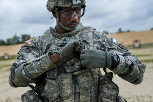 Sgt. Juan Jackson, an internment specialist from Lakewood, Wash., with the 493rd Military Police Company, makes adjustments to his vest on the M16 zero range during the 2014 Army Reserve Best Warrior Competition at Joint Base McGuire-Dix-Lakehurst, N.J., June 25. (U.S. Army photo by Sgt. 1st Class Michel Sauret)