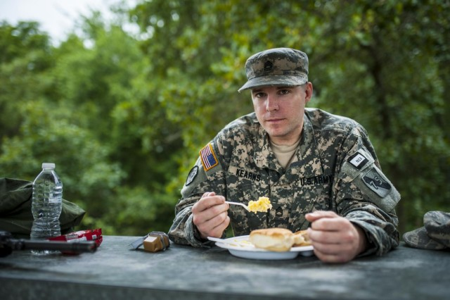 Sgt. 1st Class Timothy Kearns, a combat engineer and trainer from Houston with the 75th Training Division, eats breakfast after an 8-mile road march that started in the early morning during the 2014 Army Reserve Best Warrior Competition at Joint Base McGuire-Dix-Lakehurst, N.J., June 25. Kearns had to take a week off his work and studies toward a Ph.D. in geology from the University of Houston in order to compete in this year's event. (U.S. Army photo by Sgt. 1st Class Michel Sauret)