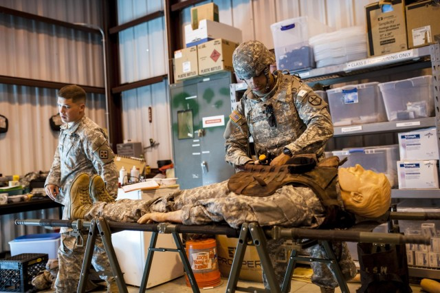 Spc. Rahmad Gholston, resident of Pullman Washington, and an air defense artillery specialist with the 301st Maneuver Enhancement Brigade, evaluates a dummy representing a casualty to see which first aid interventions are needed during the 2014 Army Reserve Best Warrior Competition at Joint Base McGuire-Dix-Lakehurst, N.J., June 24. (U.S. Army photo by Sgt. 1st Class Michel Sauret)