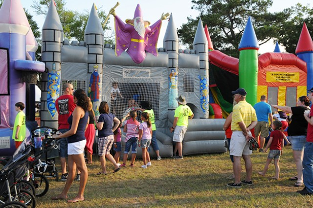 Families stand by and watch their children play in on the bounce castles July 3.