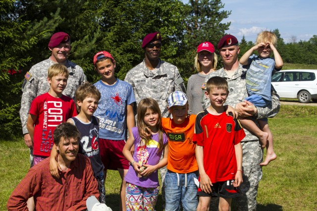 Paratroopers from 1st Squadron, 91st Cavalry Regiment, 173rd Airborne Brigade stand with Latvian children and parents at a summer camp in Ergli, Latvia, July 9, 2014. Paratroopers with the 1st Squadron, 91st Cavalry Regiment, based at Grafenwoehr Training Area, Germany, offered campers a glimpse into U.S. Army life, their equipment, meals and physical readiness training. Approximately 600 paratroopers from the brigade are in Estonia, Latvia, Lithuania and Poland as part of Operation Atlantic Resolve, an unscheduled land-forces exercise to demonstrate commitment to NATO obligations and sustain interoperability with allied forces.