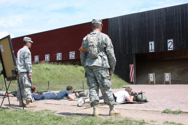 Participants in the German-American friendship  shoot take careful aim at the the target, while the Soldiers from USAG Ansbach HHD watch over them.