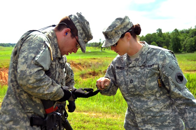 U.S. Army Sgt. 1st Class Lucenthia Warden, lane safety, squad live fire, Task Force Wolf, collects brass from a Cadet on the squad live fire lane during Cadet Summer Training (CST) on Fort Knox, Ky., July 3. The squad live fire cadre, comprised of Reserve Soldiers from Detachment 2, 2-379th, 1st Brigade, 104th Training Division, provides safety over watch necessary for the training. The squad live fire lane teaches the Cadets to perform basic tactics such as moving tactically as a squad, assessing the environment for threats, communicating effectively to their element, and engaging the targets proficiently.