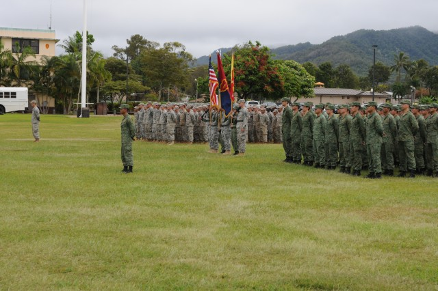 "Soldiers from 2nd Battalion, 35th Infantry Regiment ""Cacti,"" 3rd Brigade Combat Team, 25th Infantry Division, and a Singaporian rifle company, stand in formation during the opening ceremony, at Weyand Field, Schofield Barracks, Hawaii, July 14, 2014, marking the official start of Tiger Balm 2014."
