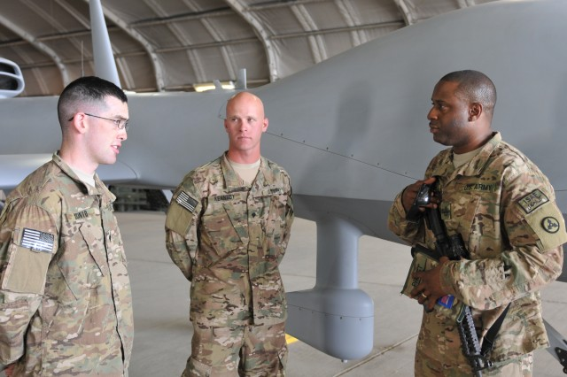 Sergeant 1st Class Lee Priest (right), the Materiel Readiness Branch  non-commissioned officer in charge and aviation maintenance manager for the 3d Sustainment Command (Expeditionary), talks with Spc. Nathan Kennedy (center), an unmanned aerial vehicle systems repairer with Task Force Gray Eagle, and Spc. Rocco Scinto (left), a UAV operator with Task Force Gray Eagle July 2 at Bagram Air Field, Afghanistan.