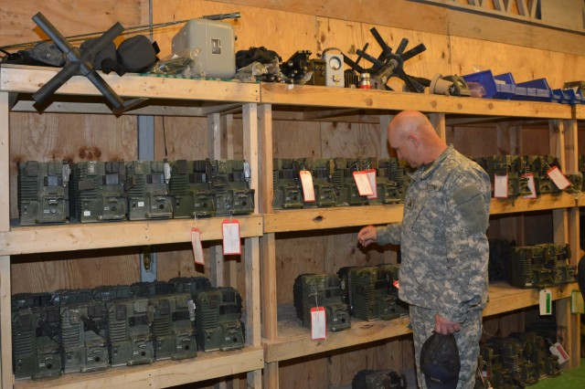 Robert L. Martin, Communications-Electronics Command Electronic Sustainment Support Center/Regional Support Center manager, looks over Harris Vehicular Amplifier Adaptors that are awaiting repair.