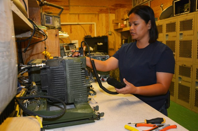 April Picart, an electronics technician, works on a Harris radio in the Communications-Electronics Command Regional Support Center Jul. 5. Many vehicles must have functioning radio communications equipment to be considered fully mission capable.