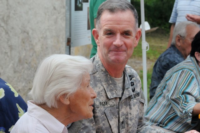 Brig. Gen. Walter E. Piatt, commanding general of the Joint Multinational Training Command, visits with original Schmidheim resident Frieda Ohneis during the annual Schmidheimer reunion in the Hohenfels Training Area, Germany, July 5, 2014.