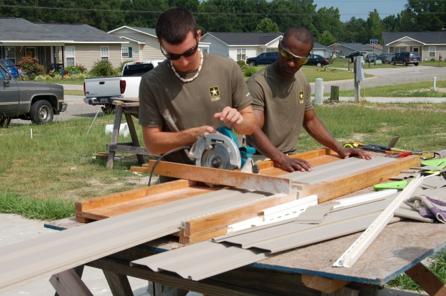 Future Soldier Tyler Harrington cuts the siding and Sgt. Jimmy Griffin of Sumter Army Recruiting Center, holds it in place.