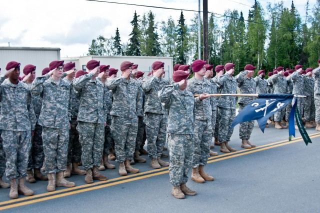 Paratroopers of the 1st Battalion (Airborne), 501st Infantry Regiment, 4th Infantry Brigade Combat Team (Airborne), 25th Infantry Division, render honors during an Honorary Command Sergeant Major Induction Ceremony at Joint Base Elmendorf-Richardson, Alaska July 14, 2014. Command Sgt. Maj. Bernie Knight, retired, was given the honorary title and serves as the link between all members the battalion currently serving and those who have served before. (Photo by U.S. Army Sgt. Eric-James Estrada/Released)