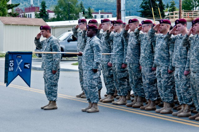 Paratroopers of the 1st Battalion (Airborne), 501st Infantry Regiment, 4th Infantry Brigade Combat Team (Airborne), 25th Infantry Division, render honors during an Honorary Command Sergeant Major Induction Ceremony at Joint Base Elmendorf-Richardson, Alaska July 14, 2014.  Command Sgt. Maj. Bernie Knight, retired, received the honorary title and serves as the link between all members in the battalion currently serving and those who have served before. (Photo by U.S. Army Sgt. Eric-James Estrada/Released)
