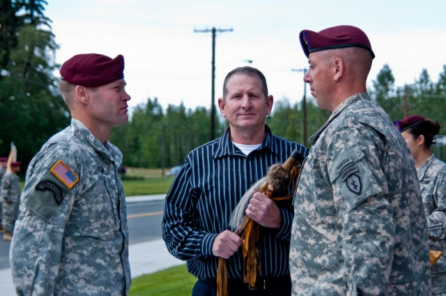Command Sgt. Maj. Bernie Knight (center), retired, holds the ceremonial Tomahawk, as he is charged as the honorary command sergeant major of the battalion during an Honorary Command Sergeant Major Induction Ceremony at Joint Base Elmendorf-Richardson, Alaska, July 14, 2014. The Tomahawk symbolizes the lethal force of the NCO Corps necessary to complete the mission, as well as resembles a primitive ice pick to reinforce the battalion's additional requirement for arctic proficiency. The honorary command sergeant major serves as the link between all members in the battalion currently serving and those who have served before.  (Photo by U.S. Army Sgt. Eric-James Estrada/Released)