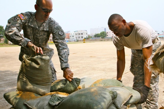 Capt. Hugh M. Jones, commander of Headquarters and Headquarters Company, 19th Expeditionary Sustainment Command, and Sgt. Billy D. Williams, assigned to Support Operations, HHC, 19th ESC, carry sand bags during the Assault Command Post set up, at Camp Walker, in Daegu, South Korea, June 30, 2014.