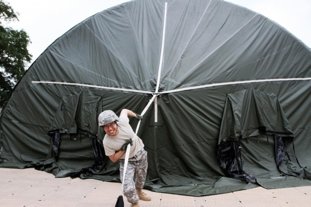 Pfc. Park, Sang-woo, training specialist, Headquaters and Headquarters Company 19th Expeditionary Sustainment Command, helps layout a new airbeam tent, during the Assault Command Post set up, at Camp Walker, in Daegu, South Korea, June 30, 2014.