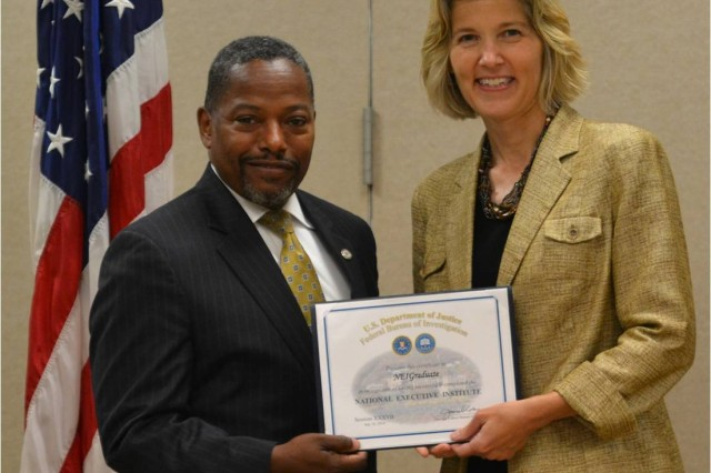 FBI Executive Assistant Director, Science and Technology, Amy Hess, presents Mr. H. Tracy Williams III, OPMG Chief of Staff, FBI National Executive Institute (NEI) Graduation Certificate