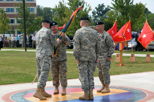 Gen. David G. Perkins, commanding general of U.S. Army Training and Doctrine Command, passes the unit colors to Lt. Gen. H. R. McMaster, incoming director of TRADOC's Army Capabilities Integration Center, during the assumption of responsibility ceremony at Fort Eustis, Va., July 15, 2014. The transfer of the colors represents the transfer of responsibility for the accomplishment of the mission and for providing for the welfare, order and discipline of the Soldiers assigned. (U.S. Air Force photo by Senior Airman Teresa J.C. Aber)