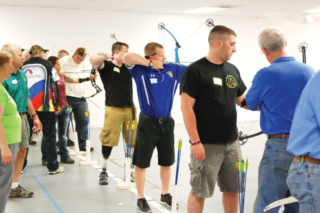 Wounded, injured and ill servicemembers from Fort Belvoir and Walter Reed National Military Medical Center learn archery skills during the Adapted Archery Day clinic, July 10, 2014 at Outdoor Recreation's archery range.