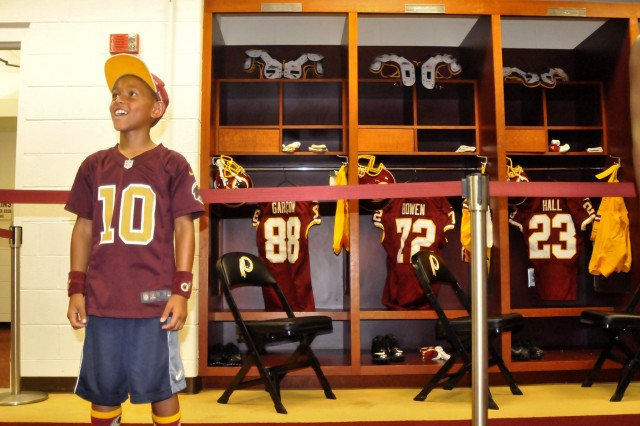 Nine-year-old Xavier Washington of Manassas, Va., is all smiles in front of Washington Redskins wide receiver Pierre Garcon's locker, during a tour of the team's locker room at the first-ever Redskins Salute Military Appreciation Day, July 13, 2014, at FedEx Field in Landover, Md. More than 3,000 service members, military veterans and their families attended the event.