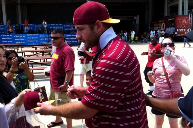 Former Washington Redskins tight end Chris Cooley signs an autograph for a military family member at the inaugural Redskins Salute Military Appreciation Day at FedEx Field in Landover, Md., July 13, 2014.