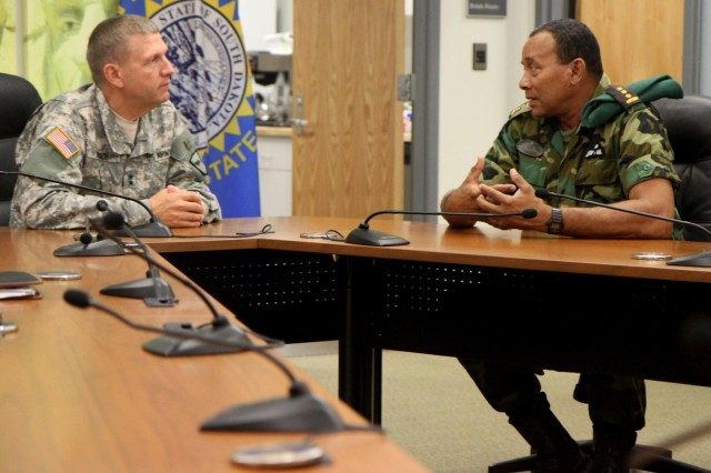 Maj. Gen Timothy Reisch, adjutant general of the South Dakota National Guard discusses with Col. Adolf Jardim, deputy commander of the Suriname Armed Forces, during the Reserve Forces Subject Matter Expert Exchange at Camp Rapid, S.D., July 11, 2014. Three leadership representatives from Suriname visited South Dakota to research how to implement a reserve military force in their home country. The partnership with Suriname was formally initiated in August 2006, to develop a mutually beneficial, long-term security cooperation relationship between the two partners.