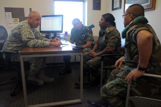 Lt. Col. Todd Bartunek, the state training officer discusses different aspects of training a reserve force with Col. Adolf Jardim, deputy commander of the Suriname armed forces, left, Maj. Sieflien Grot, head of military personnel for the Suriname armed forces, and Maj. Lesley Paul Nojodipo, head of military operations in the Suriname armed forces, as part of the Reserve Forces Subject Matter Expert Exchange at Camp Rapid, S.D. July 11, 2014. Three leadership representatives from Suriname visited South Dakota as part of the State Partnership Program to gain the knowledge to establish a reserve military component in their home country. The partnership with Suriname was formally initiated in August 2006, to develop a mutually beneficial, long-term security cooperation relationship between the two partners.