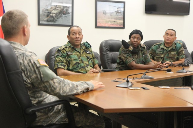 Maj. Gen. Timothy Reisch, adjutant general of the South Dakota National Guard, left, welcomes Col. Adolf Jardim, deputy commander of the Suriname armed forces, Maj. Sieflien Grot, head of military personnel for the Suriname armed forces, and Maj. Lesley Paul Nojodipo, head of military operations in the Suriname armed forces, to South Dakota during the Reserve Forces Subject Matter Expert Exchange at Joint Forces Headquarters on Camp Rapid, S.D., July 11, 2014. The partnership with Suriname was formally initiated in August 2006, to develop a mutually-beneficial, long-term security cooperation relationship between the two partners.
