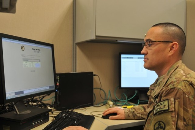 Chief Warrant Officer 2 Walter Keen, a human resources technician with the 3d Sustainment Command (Expeditionary), updates a Soldier's award through eMILPO June 25 on Bagram Air Field, Afghanistan