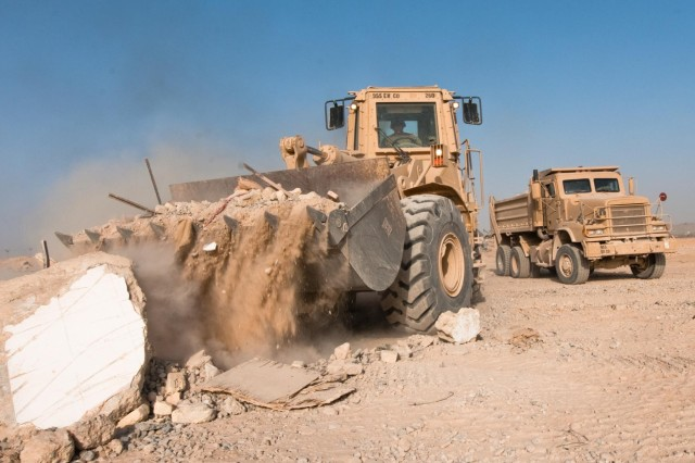 Sgt. Lewis Hernandez loads debris with his front-end loader into a 20-ton dump truck driven by Sgt. Nicholas Klowetter and Sgt. Shane Garcia, all whom serve with the 687th Engineer Company, 1st Maneuver Enhancement Brigade, during base closure operations on Forward Operating Base Walton, in Kandahar Province, Afghanistan, July 15, 2014. The FOB served as a strategic joint operating base with Afghan National Security Forces during Operation Enduring Freedom, and was officially closed two days later.